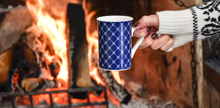 Holding drink in front of fireplace
